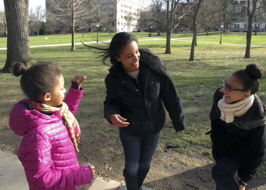 In this Monday, March 21, 2016 photo, Adelaida Torres, center, shares a laugh with daughters Elizabeth, left, and Gloria, right, in Hartford, Conn. Torres believes she never would have won custody of her two daughters in 2013 during a bitter court fight with her now-ex-husband if not for the free legal help attorney Linda Allard and Greater Hartford Legal Aid. Connecticut lawmakers are considering a bill that would create a task force to look into expanding the right to free lawyers for the poor in civil cases. (AP Photo/Dave Collins)