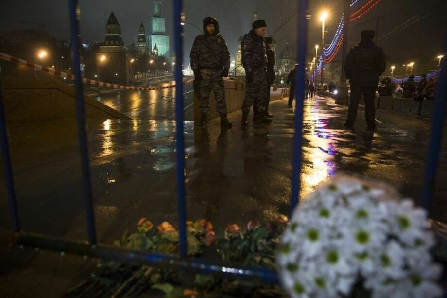 Flowers lie on the ground as Russian police officers stand near the place where Boris Nemtsov, a former Russian deputy prime minister and opposition leader, was kiiled at Red Square with the Kremlin Wall in the background in Moscow, Russia, Saturday, Feb. 28, 2015. Nemtsov, sharp critic of President Vladimir Putin, was gunned down Saturday, just a day before a planned protest against the government. The death of Nemtsov ignited a fury among opposition figures who assailed the Kremlin for creating an atmosphere of intolerance of any dissent and called the killing an assassination. Putin quickly offered his condolences and called the murder a provocation. (AP Photo/Pavel Golovkin)