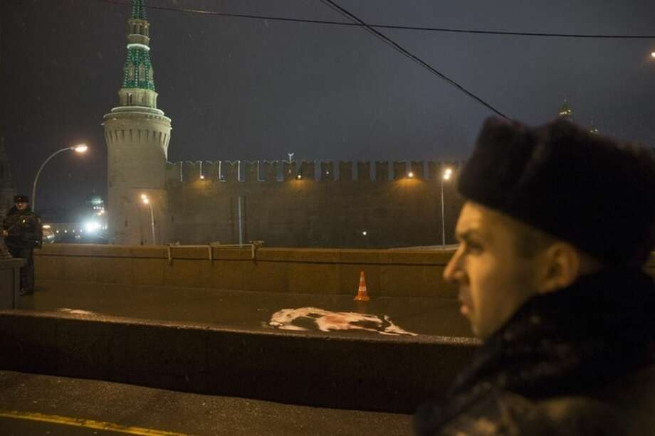 Russian police officers stand next to traces of the body of Boris Nemtsov, a former Russian deputy prime minister and opposition leader, at Red Square with the Kremlin Wall in the background in Moscow, Russia, Saturday, Feb. 28, 2015. Nemtsov, sharp critic of President Vladimir Putin, was gunned down Saturday, just a day before a planned protest against the government. The death of Nemtsov ignited a fury among opposition figures who assailed the Kremlin for creating an atmosphere of intolerance of any dissent and called the killing an assassination. Putin quickly offered his condolences and called the murder a provocation. (AP Photo/Pavel Golovkin)