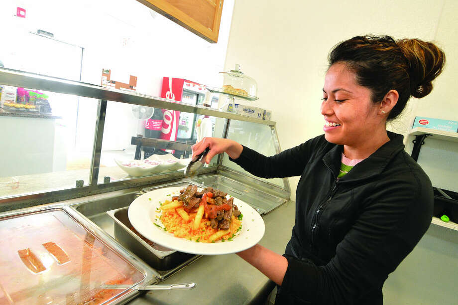 Hour Photo/Alex von Kleydorff Cecila Lucero makes a trditional Peruvian Lomo Saltado, Steak over rice and french fries for a customer at BLT Deli on Winfield St. in East Norwalk