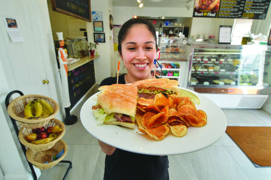 Hour Photo/Alex von Kleydorff Bernice Campos brings out an authentic Cuban sandwich at BLT Deli on Winfield St. in East Norwalk
