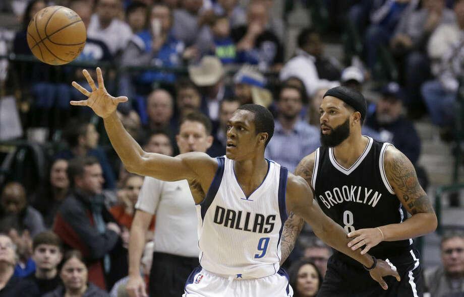 Dallas Mavericks guard Rajon Rondo (9) reaches for a pass against Brooklyn Nets guard Deron Williams (8) during the first half of an NBA Basketball game Saturday, Feb. 28, 2015, in Dallas. (AP Photo/LM Otero)