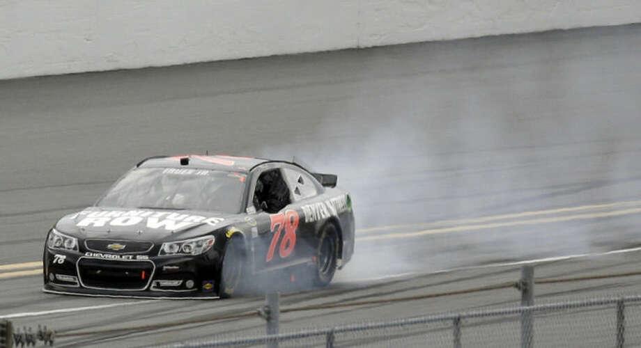 Smokes billows from the car of Martin Truex Jr. during the NASCAR Daytona 500 Sprint Cup series auto race at Daytona International Speedway in Daytona Beach, Fla., Sunday, Feb. 23, 2014. (AP Photo/John Raoux)