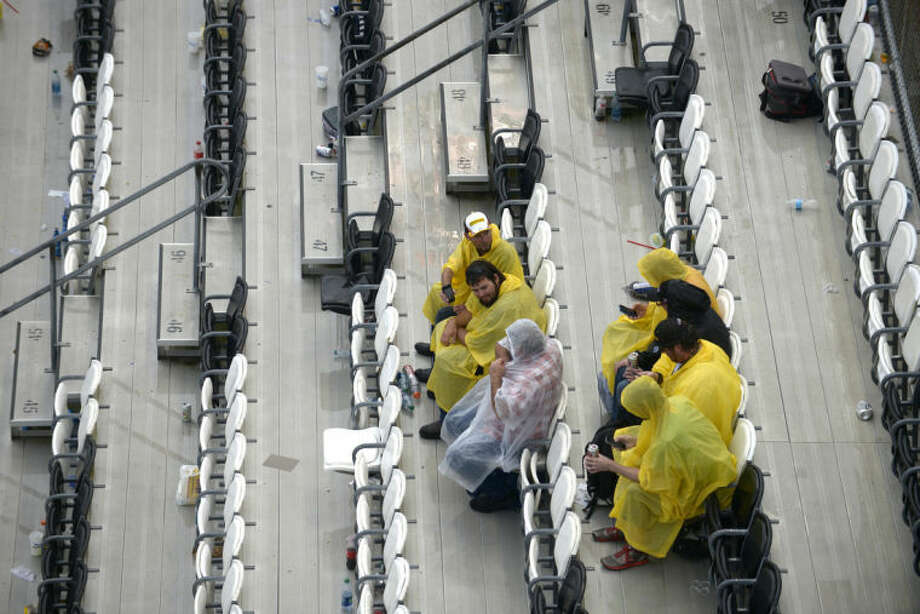 Race fans take cover from the rain in the stands during the NASCAR Daytona 500 auto race at Daytona International Speedway in Daytona Beach, Fla., Sunday, Feb. 23, 2014. (AP Photo/Phelan M. Ebenhack)