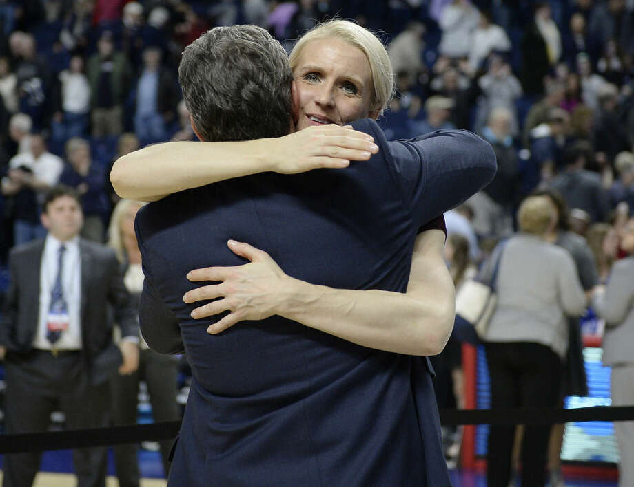 In this March 28, 2016 photo, Connecticut assistant coach Shea Ralph embraces coach Geno Auriemma after UConn defeated Texas in the regional final of the women's NCAA basketball tournament in Bridgeport, Conn. Ralph, a former UConn player and national player of the year, has been coaching with Auriemma at UConn for seven seasons. (AP Photo/Jessica Hill)