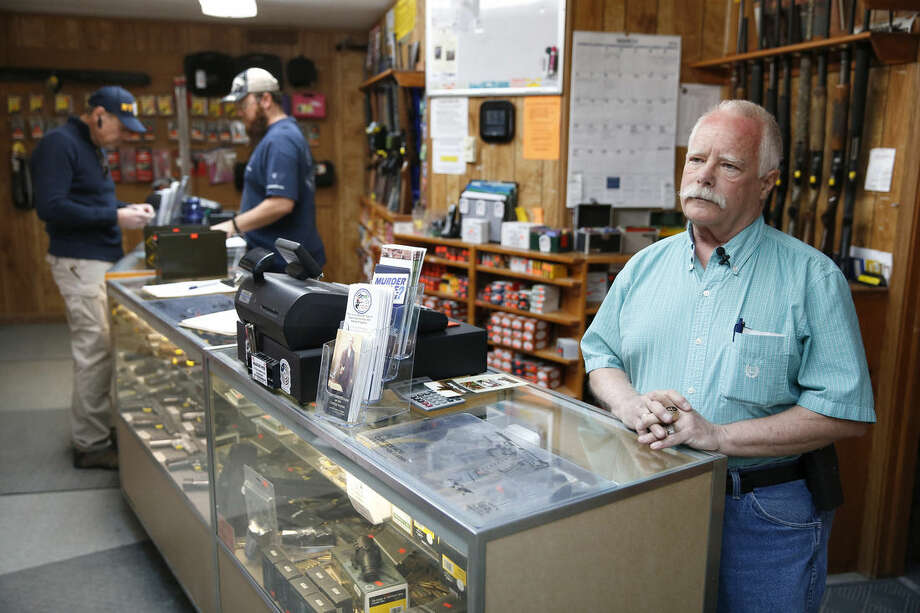 """In this March 15, 2016 photo, Doug Hamilton, right, the owner of the Family Shooting Center, stands behind the counter at his shooting range, at Cherry Creek State Park, Colo. Hamilton was present on the day when two tourists, Australian twin sisters, attempted suicide using rented guns at his range, one dying from her wounds. Hamilton is open to letting his staff get some suicide-prevention training, though he's unsure it would help. Those who killed themselves at his range exhibited no signs of stress beforehand. """"How do we identify a bad apple who's about to go over the edge, and get them the help that they need?"""" Hamilton asked. """"Suicide prevention brochures aren't something that anyone's going to pick up who has come out to our range to kill themselves."""" (AP Photo/Brennan Linsley)"""