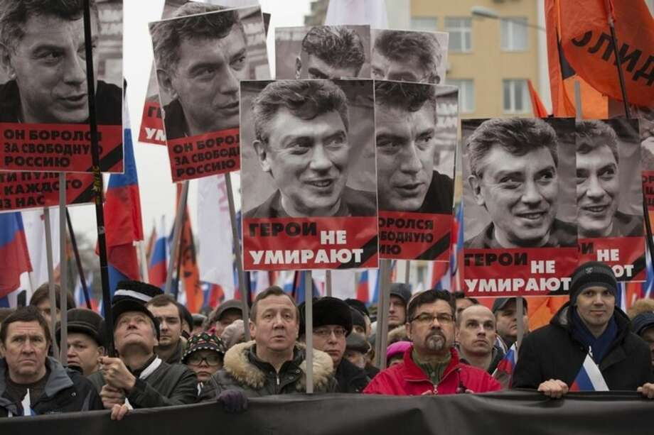 People march in memory of opposition leader Boris Nemtsov who was gunned down on Friday, Feb. 27, 2015 near the Kremlin, with portraits of him and words reading 'he died for the freedom to Russia, heroes never die!' in Moscow, Russia, Sunday, March 1, 2015. Russian investigators, politicians and political commentators on state television on Saturday covered much ground in looking for the reason Nemtsov was gunned down in the heart of Moscow, but they sidestepped one possibility, that he was murdered for his relentless opposition to Putin. (AP Photo/Pavel Golovkin)