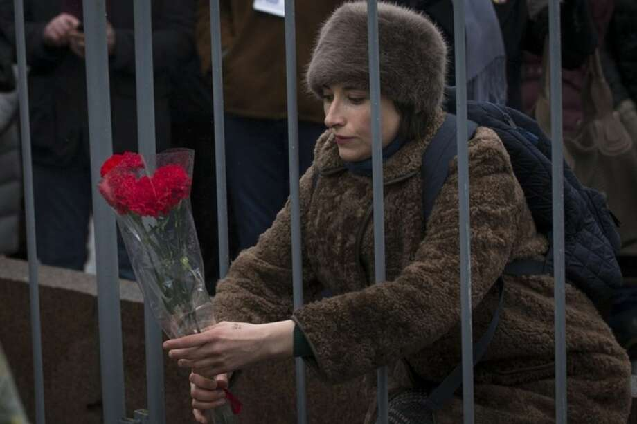 "A woman lays flowers at the place where Boris Nemtsov, a charismatic Russian opposition leader and sharp critic of President Vladimir Putin, was gunned down on Friday, Feb. 27, 2015 near the Kremlin, in Moscow, Russia, Sunday, March 1, 2015. Thousands converged Sunday in central Moscow to mourn veteran liberal politician Boris Nemtsov, whose killing on the streets of the capital has shaken Russia's beleaguered opposition. They carried flowers, portraits and white signs that said ""I am not afraid."" (AP Photo/Pavel Golovkin)"