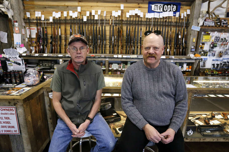 In this Feb. 23, 2016 photo, Police Commander Keith Caddy, right, sits with Gun Depot shop manager Bobby Gray in Montrose Colo, where suicide rates are among the highest in the nation. Caddy has been around guns since childhood as a hunter, lawman, firearms instructor and licensed gun seller. Now he's doing outreach for the Gun Shop Project, and most of the businesses he has visited agreed to display the suicide-awareness materials once they were assured it wasn't a gun-takeaway program in disguise. (AP Photo/Brennan Linsley)