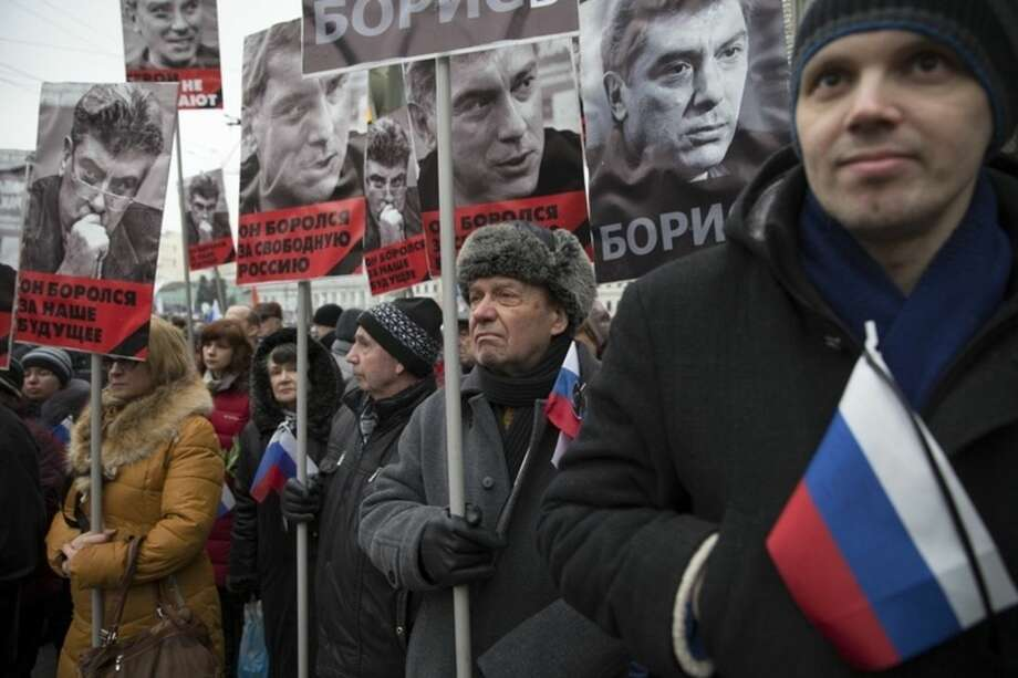 People carry portraits of opposition leader Boris Nemtsov who was gunned down on Friday, Feb. 27, 2015 near the Kremlin, with words reading ' He fought for a free of Russia, He fought for our future !' in Moscow, Russia, Sunday, March 1, 2015. Russian investigators, politicians and political commentators on state television on Saturday covered much ground in looking for the reason Nemtsov was gunned down in the heart of Moscow, but they sidestepped one possibility, that he was murdered for his relentless opposition to Putin. (AP Photo/Pavel Golovkin)
