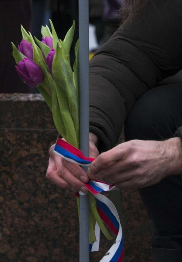 "A man ties a bunch of flowers with a ribbon in the colours of the Russian national fag at the place where Boris Nemtsov, a charismatic Russian opposition leader and sharp critic of President Vladimir Putin, was gunned down on Friday, near the Kremlin, in Moscow, Russia, Sunday, March 1, 2015. Thousands converged Sunday in central Moscow to mourn veteran liberal politician Boris Nemtsov, whose killing on the streets of the capital has shaken Russia's beleaguered opposition. They carried flowers, portraits and white signs that said ""I am not afraid."" (AP Photo/Pavel Golovkin)"