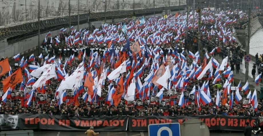 "People carry a huge banner reading 'those bullets for everyone of us, heroes never die!' as they march in memory of opposition leader Boris Nemtsov who was gunned down on Friday, Feb. 27, 2015 near the Kremlin, in Moscow, Russia, Sunday, March 1, 2015. Thousands converged Sunday in central Moscow to mourn veteran liberal politician Boris Nemtsov, whose killing on the streets of the capital has shaken Russia's beleaguered opposition. They carried flowers, portraits and white signs that said ""I am not afraid."" (AP Photo/Dmitry Lovetsky)"