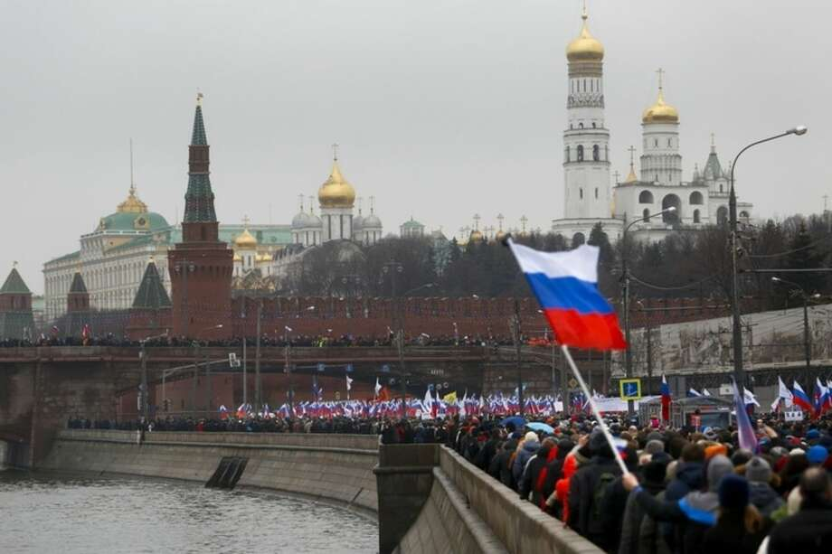 "People with Russian national flags march in memory of opposition leader Boris Nemtsov, who was gunned down on Friday, Feb. 27, 2015 near the Kremlin, in Moscow, Russia, Sunday, March 1, 2015. Thousands converged Sunday in central Moscow to mourn veteran liberal politician Boris Nemtsov, whose killing on the streets of the capital has shaken Russia's beleaguered opposition. They carried flowers, portraits and white signs that said ""I am not afraid."" (AP Photo/Denis Tyrin)"