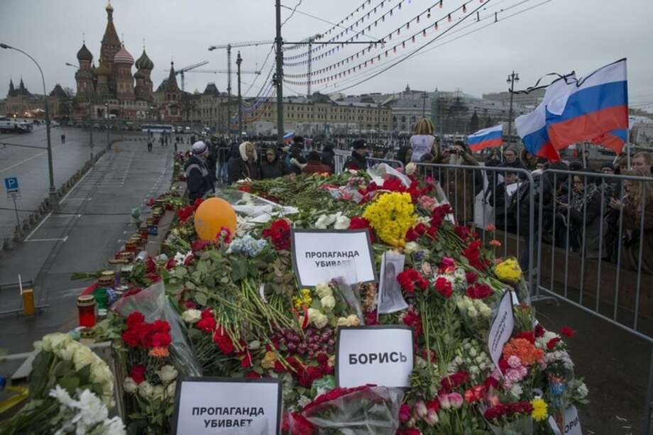 Flowers and pesters reading 'propaganda kills! Fight!' are seen at the place where Boris Nemtsov, a charismatic Russian opposition leader and sharp critic of President Vladimir Putin, was gunned down on Friday, Feb. 27, 2015 near the Kremlin, with St, Basil Cathedral is in the background in Moscow, Russia, Sunday, March 1, 2015. Russian investigators, politicians and political commentators on state television on Saturday covered much ground in looking for the reason Nemtsov was gunned down in the heart of Moscow, but they sidestepped one possibility, that he was murdered for his relentless opposition to Putin. (AP Photo/Pavel Golovkin)