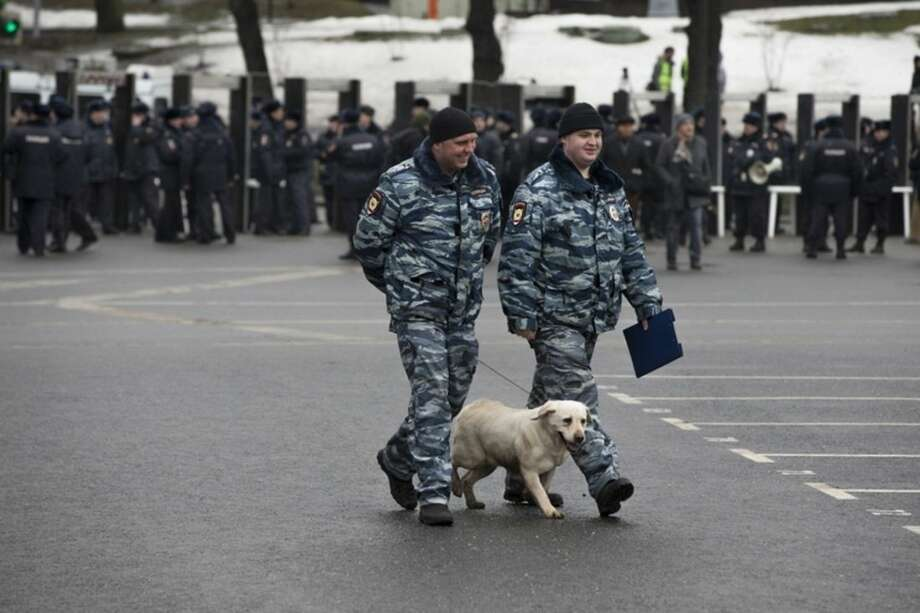 Police officers walk with their sniffing dog checking the area prior a march in memory of opposition leader Boris Nemtsov, who was gunned down on Friday, Feb. 27, 2015 near the Kremlin, in Moscow, Russia, Sunday, March 1, 2015. Russian investigators, politicians and political commentators on state television on Saturday covered much ground in looking for the reason Nemtsov was gunned down in the heart of Moscow, but they sidestepped one possibility, that he was murdered for his relentless opposition to Putin. (AP Photo/Pavel Golovkin)