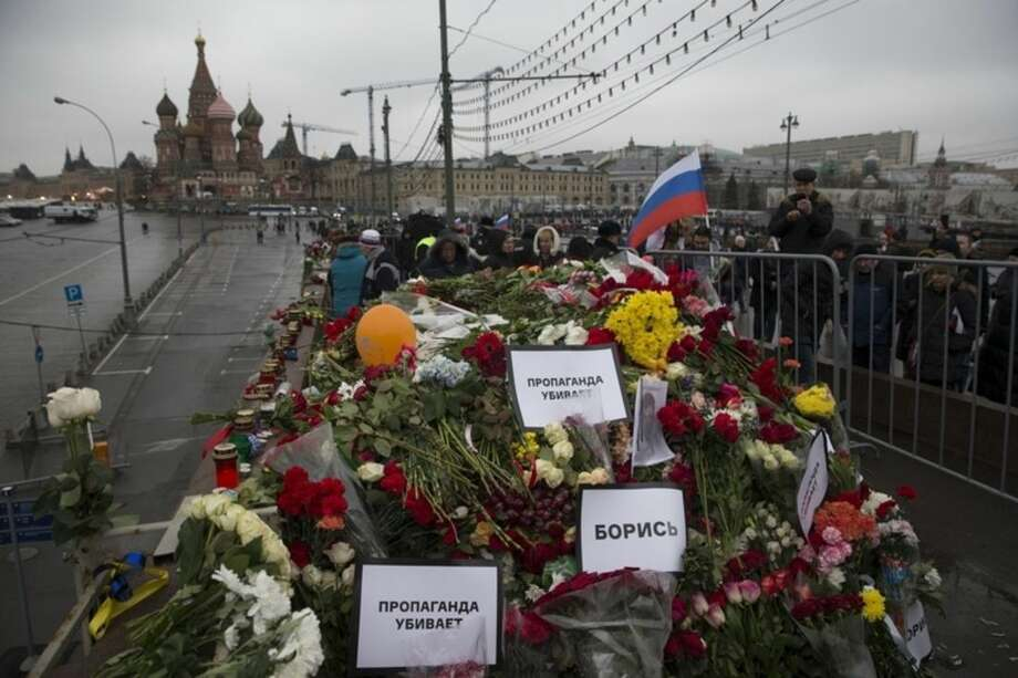 Flowers and pesters reading ' propaganda kills!' are seen at the place where Boris Nemtsov, a charismatic Russian opposition leader and sharp critic of President Vladimir Putin, was gunned down on Friday, Feb. 27, 2015 near the Kremlin, with the Kremlin Wall is in the background in Moscow, Russia, Sunday, March 1, 2015. Russian investigators, politicians and political commentators on state television on Saturday covered much ground in looking for the reason Nemtsov was gunned down in the heart of Moscow, but they sidestepped one possibility, that he was murdered for his relentless opposition to Putin. (AP Photo/Pavel Golovkin)