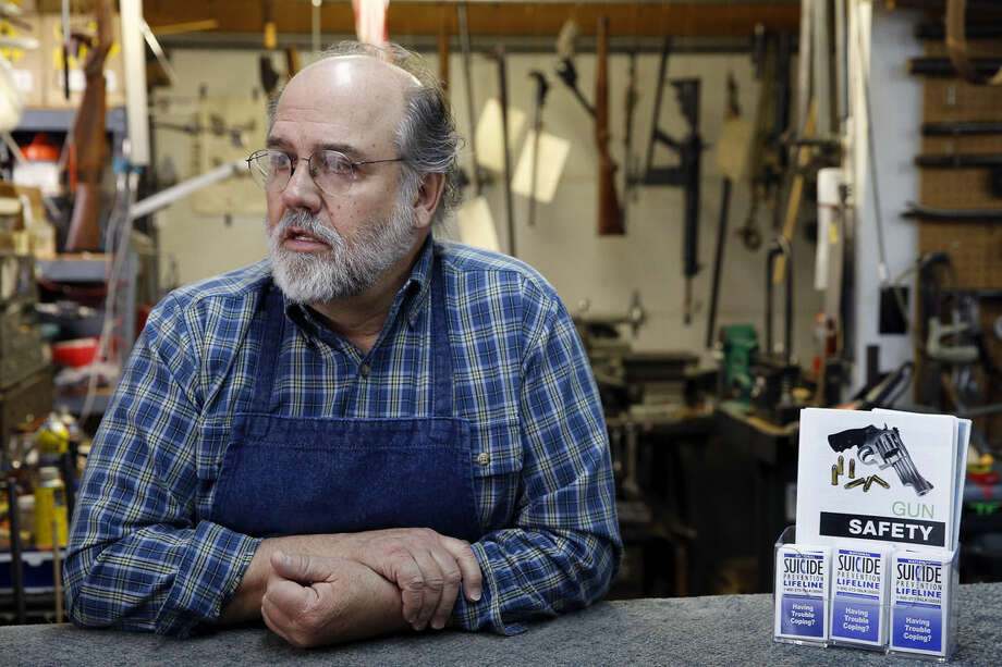 In this Feb. 23, 2016 photo, expert gunsmith Keith Carey stands behind the counter at his shop, where he makes suicide prevention literature available, in Montrose Colo. Carey is a staunch, though soft-spoken, defender of the right to bear arms, sharing the worries of many in the region that gun control would debilitate America. Yet he's also a willing recruit in a fledgling effort to see if the gun community itself - sellers and owners of firearms, operators of shooting ranges - can help Colorado and a swath of other Western states reduce their highest-in-the-nation suicide rates. (AP Photo/Brennan Linsley)
