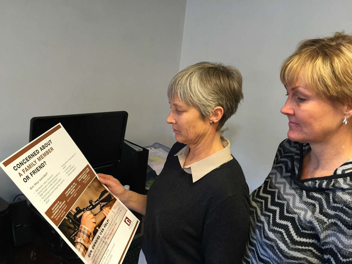 AP Photo/David Crary Martha Graf, left, executive director of the Western Colorado Suicide Prevention Foundation, and Cindy Haerle, a board member of the foundation, look at one of the suicide-prevention posters that are being distributed to gun shops and shooting ranges in and around Grand Junction, Colorado. Haerle's brother, John, killed himself with a pistol shot when he was 29 after prolonged struggles with depression.
