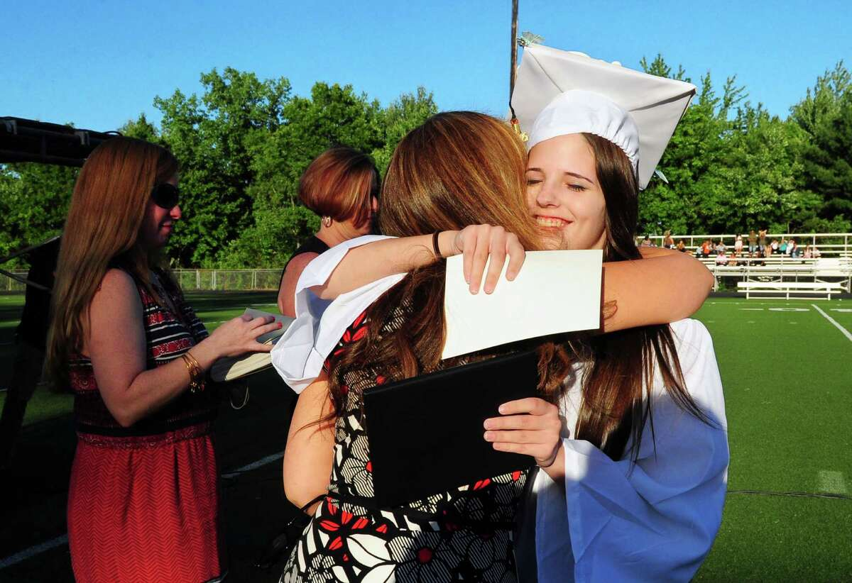 Graduate Taylor Blakenship hugs her teacher after getting her diploma during Shelton High School's Class of 2016 Commencement Exercises in Shelton, Conn., on Friday June 10, 2016.
