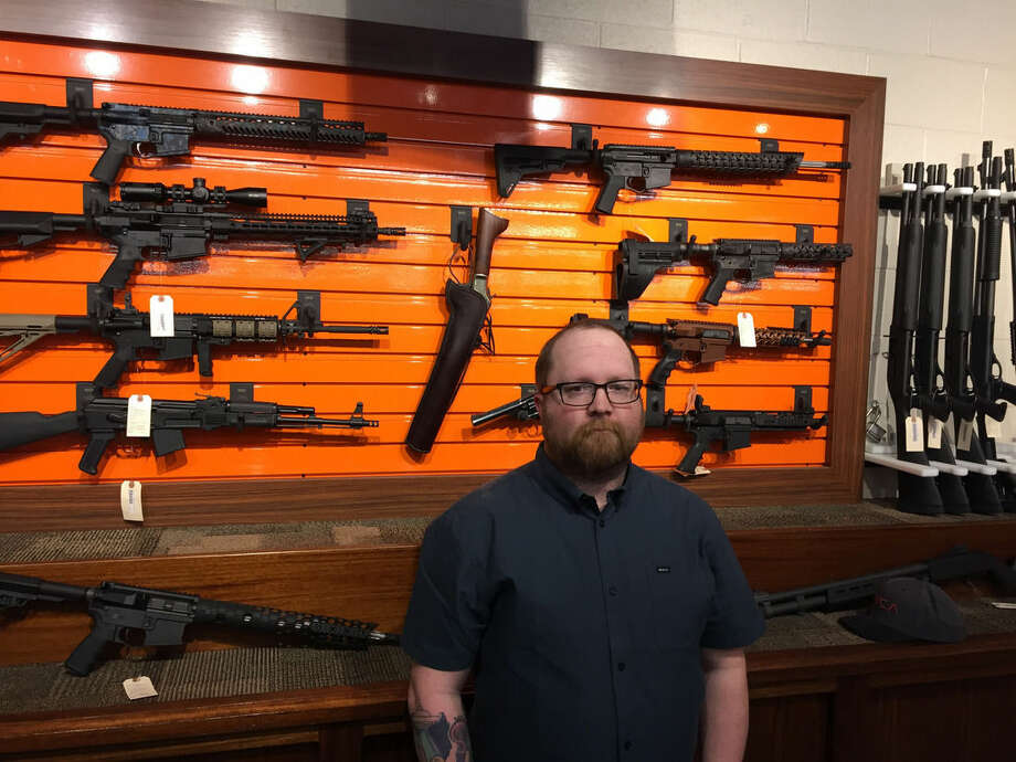 Josh O'Neal, general manager of the Rocky Mountain Gun Club in Grand Junction, Colorado, stands in front of a display of firearms at the state-of-the-art shooting range. O'Neal says safety is a high priority at the facility, but he and his staff are apprehensive regarding the possibility that a suicidal person might rent a gun at the site and then kill themselves. (AP Photo/David Crary)