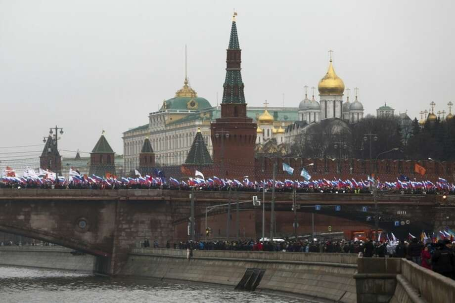 """People with Russian national flags march in memory of opposition leader Boris Nemtsov who was gunned down on Friday, near the Kremlin, with the Kremlin in the background in Moscow, Russia, Sunday, March 1, 2015. Thousands converged Sunday in central Moscow to mourn veteran liberal politician Boris Nemtsov, whose killing on the streets of the capital has shaken Russia's beleaguered opposition. They carried flowers, portraits and white signs that said """"I am not afraid."""" (AP Photo/Denis Tyrin)"""