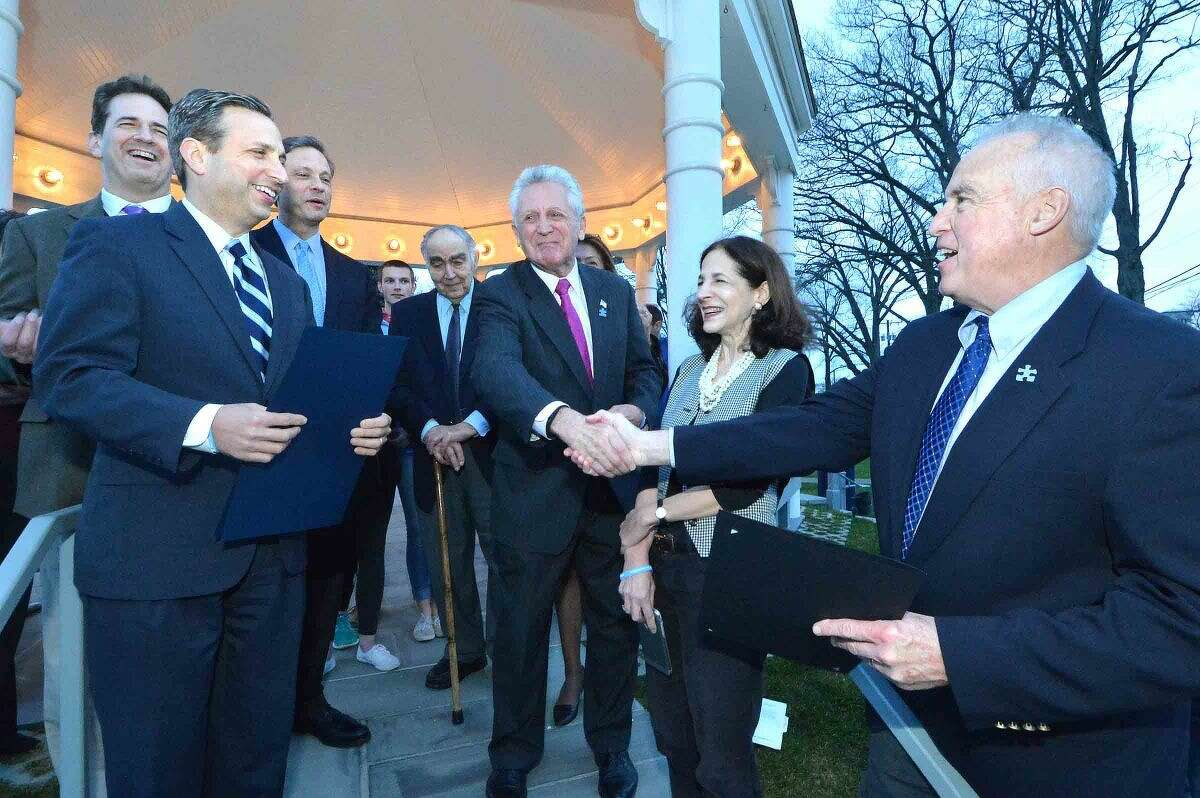Hour Photo/Alex von Kleydorff Norwalk Mayor Harry Rilling along with Senator Bob Duff read proclamations to kick off April as Autism Awareness Month and shake hands with the President of Norwalk Sped Partners Jeff Spahr as the Gazebo on the Town Green is lighted blue