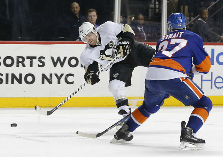 Pittsburgh Penguins right wing Phil Kessel (81) shoots to score a goal as New York Islanders defenseman Brian Strait (37) defends during the third period of an NHL hockey game, Saturday, April 2, 2016, in New York. The Penguins won 5-0. (AP Photo/Julie Jacobson)