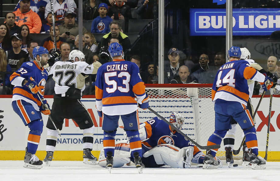 New York Islanders goalie Jean-Francois Berube (30) watches as the puck rebounds out of the goal after the Pittsburgh Penguins scored during the second period of an NHL hockey game, Saturday, April 2, 2016, in New York. (AP Photo/Julie Jacobson)