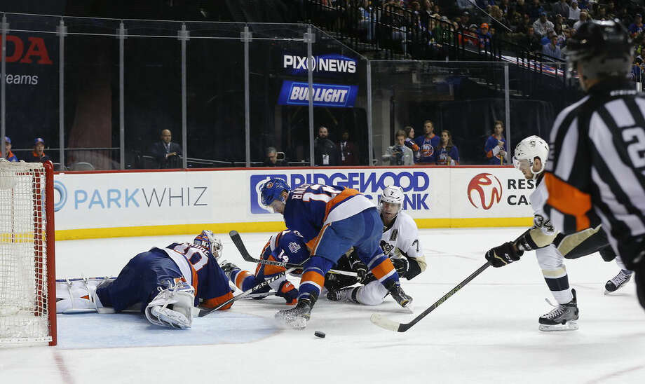 Pittsburgh Penguins right wing Tom Kuhnhackl (34) reaches out to knock in a rebound for a goal against New York Islanders goalie Jean-Francois Berube (30) during the third period of an NHL hockey game, Saturday, April 2, 2016, in New York. The Penguins won 5-0. (AP Photo/Julie Jacobson)