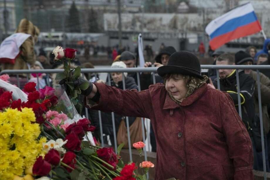 A woman lays flowers at the place where Boris Nemtsov, a charismatic Russian opposition leader and sharp critic of President Vladimir Putin, was gunned down on Friday, Feb. 27, 2015 near the Kremlin, in Moscow, Russia, Sunday, March 1, 2015. Russian investigators, politicians and political commentators on state television on Saturday covered much ground in looking for the reason Nemtsov was gunned down in the heart of Moscow, but they sidestepped one possibility, that he was murdered for his relentless opposition to Putin. (AP Photo/Pavel Golovkin)