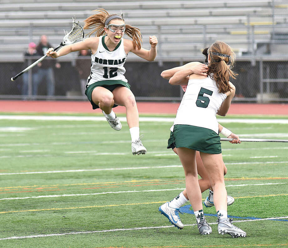 Norwalk High's Emma Larchevesque, left, leaps in celebration while joining teammates Hannah Froelich (5) and Marissa Mastrianni (obscured) after Mastrianni's game-tying goal with seven seconds left in Saturday's 8-8 tie against Stamford at Testa Field in Norwalk.