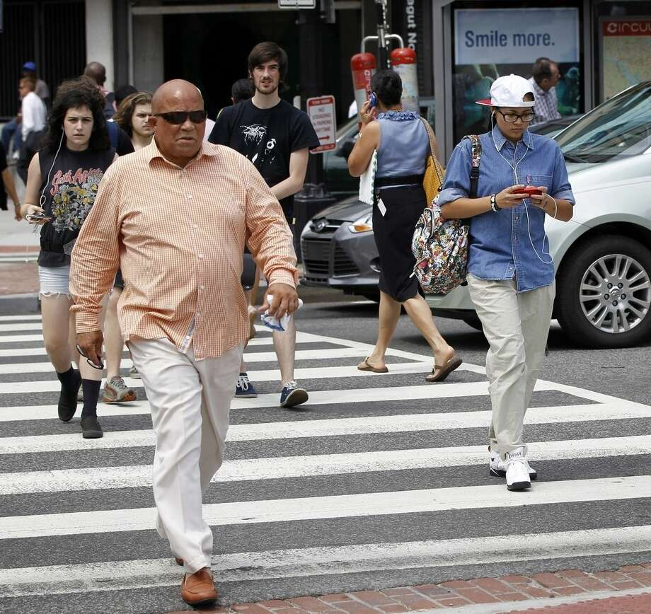 FILE - In this July 10,, 2012 file photo, a pedestrians text messages while crossing the street in downtown Washington. A New Jersey lawmaker is targeting distracted walking. The proposed measure would ban walking while texting and bar pedestrians on public roads from using electronic devices unless they are hands-free. (AP Photo/Pablo Martinez Monsivais)