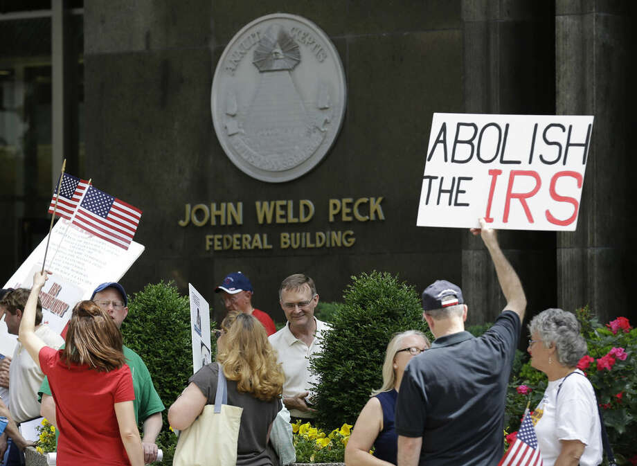 FILE - In this May 21, 2013, file photo, Tea party activists demonstrate outside the John Weld Peck Federal Building that houses the main offices for the Internal Revenue Service in Cincinnati. Tea party activists are heartened by a federal appeals court ruling that strengthens their legal push against the Internal Revenue Service for alleged targeting in past election cycles. (AP Photo/Al Behrman, File)
