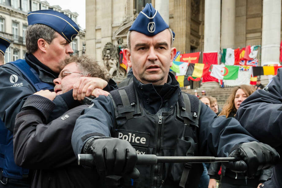 Police detain a person at the Place de la Bourse in Brussels, Belgium, Saturday, April 2, 2016. Authorities had banned all marches in Brussels, after a far-right group announced its plans to hold an anti-Muslim rally in the city. (AP Photo/Geert Vanden Wijngaert)