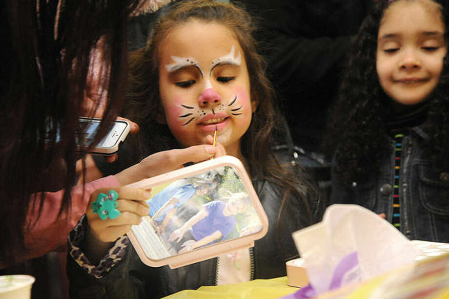 Isabelle Galeano 6, checks out her new bunny makeup Sunday where Latinos Unidos of Connecticut celebrated Easter at the South Norwalk Community Center. Hour photo/Matthew Vinci