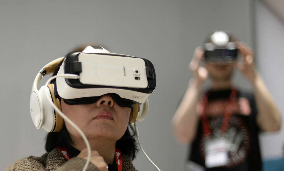 A woman uses Samsung Gear vr during the Mobile World Congress, the world's largest mobile phone trade show in Barcelona, Spain, Monday, March 2, 2015. (AP Photo/Manu Fernandez)