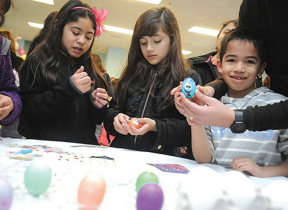 Stephanie Mesa 10, Samantha Flores 9 and Ottmar Toledo 6, painting Easter eggs at the South Norwalk Community Center where Latinos Unidos of Connecticut celebrated Easter.Hour photo/Matthew Vinci
