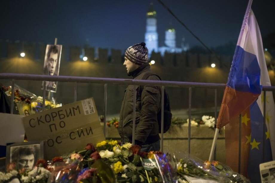 A man walks past the place decorated by a Russian national flag with European Union stars on it, where Boris Nemtsov, a charismatic Russian opposition leader and sharp critic of President Vladimir Putin, was gunned down on Friday, Feb. 27, 2015 near the Kremlin, with the Kremlin is in Moscow, Russia, Monday, March 2, 2015. The investigation into the killing of Boris Nemtsov, a fierce critic of Russian President Vladimir Putin who was gunned down not far from the Kremlin, faced conflicting reports Monday about possible surveillance footage of his slaying. Words on a poster on the left reading ' mourn for Russia '. (AP Photo/Alexander Zemlianichenko)