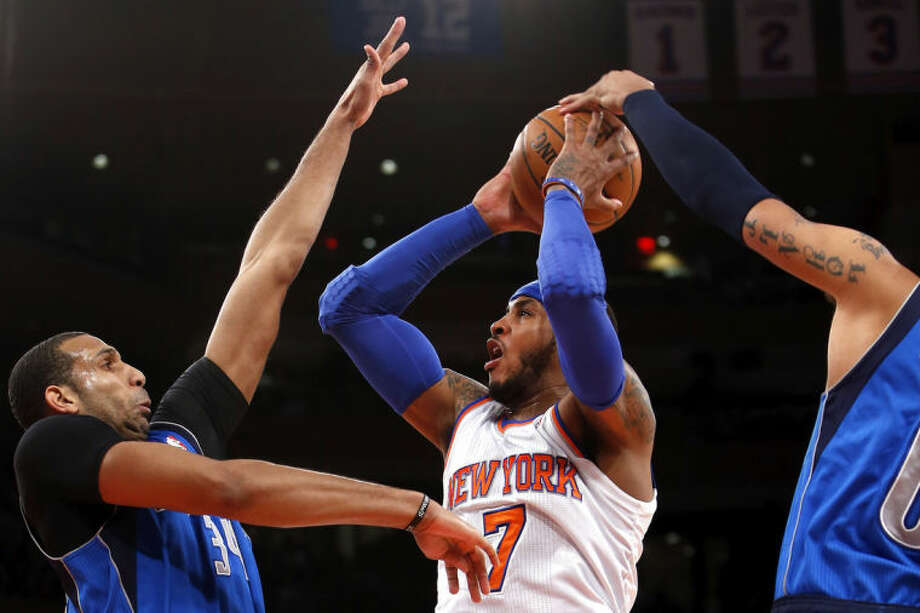New York Knicks' Carmelo Anthony (7) shoots against Dallas Mavericks' Brandan Wright, left, and Shawn Marion during the first half of an NBA basketball game, Monday, Feb. 24, 2014, in New York. (AP Photo/Jason DeCrow)