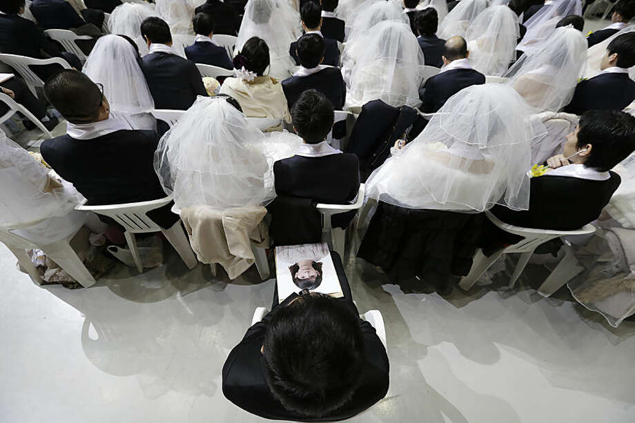 An unidentified bridegroom, bottom, holds a picture of his bride who didn't show up in a mass wedding ceremony at the Cheong Shim Peace World Center in Gapyeong, South Korea, Tuesday, March 3, 2015. Some 3,800 South Korean and foreign couples exchanged or reaffirmed marriage vows in the Unification Church's mass wedding arranged by Hak Ja Han Moon, wife of the late Rev. Sun Myung Moon, the controversial founder of the Unification Church. (AP Photo/Ahn Young-joon)