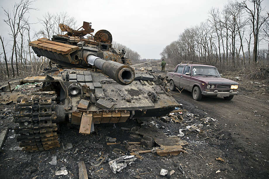 """A car passes a destroyed tank abandoned on the road at a former Ukrainian army checkpoint that was overran last month by Russia-backed separatists during the offensive for Debaltseve, outside the city of Chornukhyne, Ukraine, Monday, March 2, 2015. More than 6,000 people have died in eastern Ukraine since the start of the conflict almost a year ago that has led to a """"merciless devastation of civilian lives and infrastructure,"""" the U.N. human rights office said Monday. (AP Photo/Vadim Ghirda)"""