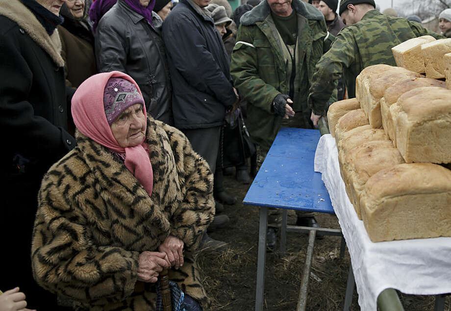 "An elderly woman looks as bread, baked by Russia-backed separatists, is brought to be delivered to residents in Chornukhyne, Ukraine, Monday, March 2, 2015. More than 6,000 people have died in eastern Ukraine since the start of the conflict almost a year ago that has led to a ""merciless devastation of civilian lives and infrastructure,"" the U.N. human rights office said Monday. (AP Photo/Vadim Ghirda)"