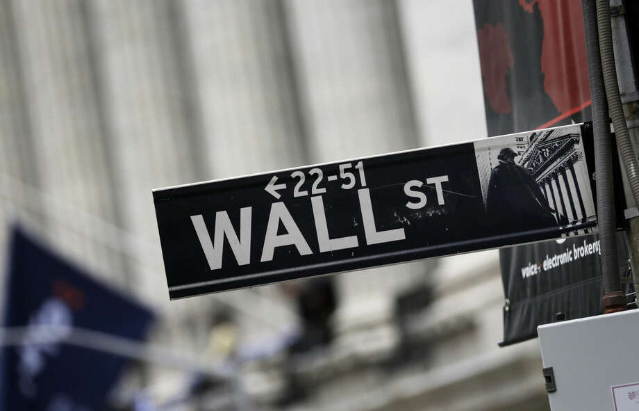 FILE - This Oct. 2, 2014, file photo, shows a Wall Street sign adjacent to the New York Stock Exchange. Stocks are edging mostly higher in early trading, Monday, March 28, 2016. Markets are generally quiet with trading closed across Europe for the Easter holiday. (AP Photo/Richard Drew, File)
