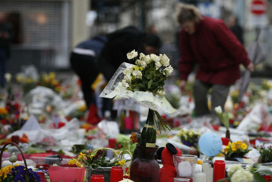 A woman helps re-adjust the tributes left for the victims of the recent bomb attacks in Brussels, following heavy rain in the Place de la Bourse in Brussels, Monday, March, 28, 2016. The Belgian health minister says four of those wounded in the suicide bombings last week have died in the hospital.(AP Photo/Alastair Grant)