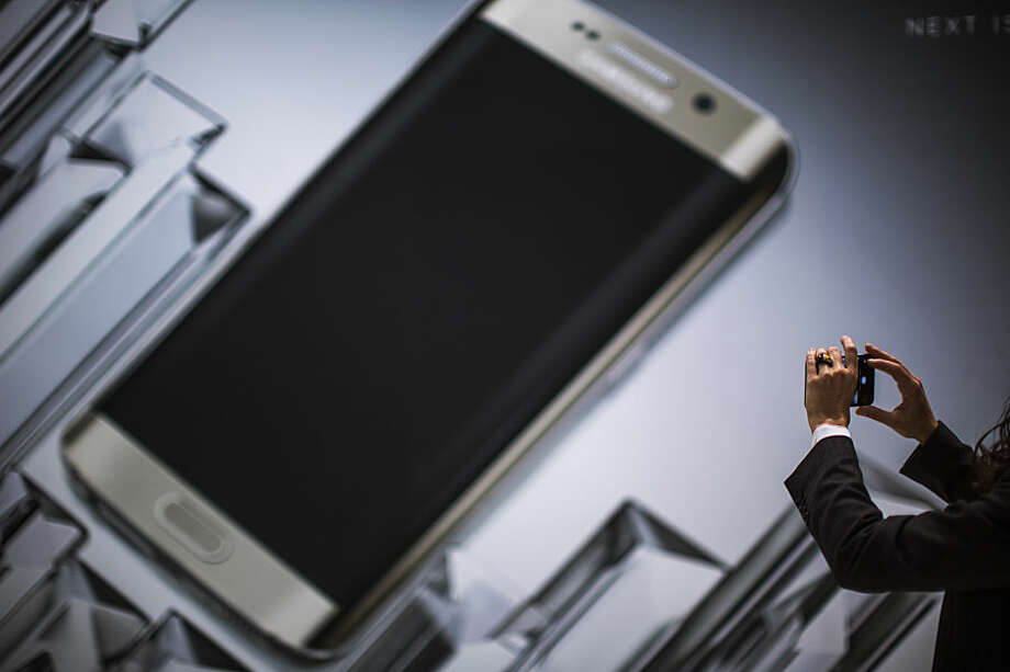 A woman takes a photo of the new Galaxy S6 during the Mobile World Congress, the world's largest mobile phone trade show in Barcelona, Spain, Monday, March 2, 2015. (AP Photo/Emilio Morenatti)