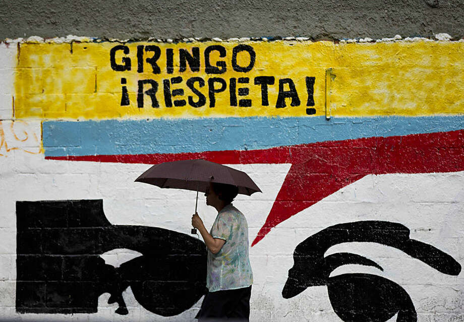 """A woman using an umbrella during a drizzle walks by a mural representing the eyes of Venezuela's independence hero Simon Bolivar that reads in Spanish """"Gringo, respect!"""" in Caracas, Venezuela, Monday, March 2, 2015. Venezuela's government has given the U.S. two weeks to slash the size of its mission here to 17 diplomats as tensions between the two nations rise. (AP Photo/Ariana Cubillos)"""