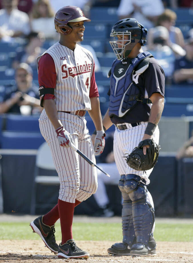 Florida State's Jameis Winston, left, laughs as he walks past New York Yankees catcher Gary Sanchez after breaking his bat in the sixth inning a spring training exhibition game Tuesday, Feb. 25, 2014, in Tampa, Fla. Winston is the 2013 Heisman Trophy winner. (AP Photo/Chris O'Meara)