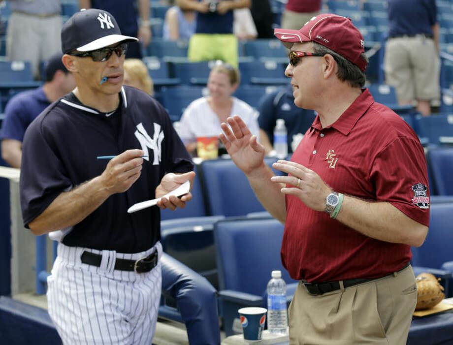 Florida State head football coach Jim Fisher, right, talks to New York Yankees manager Joe Girardi before a spring training exhibition game Tuesday, Feb. 25, 2014, in Tampa, Fla. Fisher threw out the ceremonial first pitch before the exhibition game. (AP Photo/Chris O'Meara)