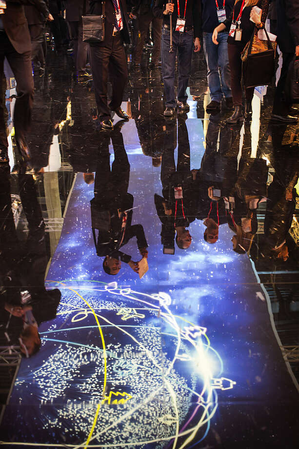 Visitors are reflected on the floor of a pavilion at the Mobile World Congress, the world's largest mobile phone trade show in Barcelona, Spain, Monday, March 2, 2015. (AP Photo/Emilio Morenatti)