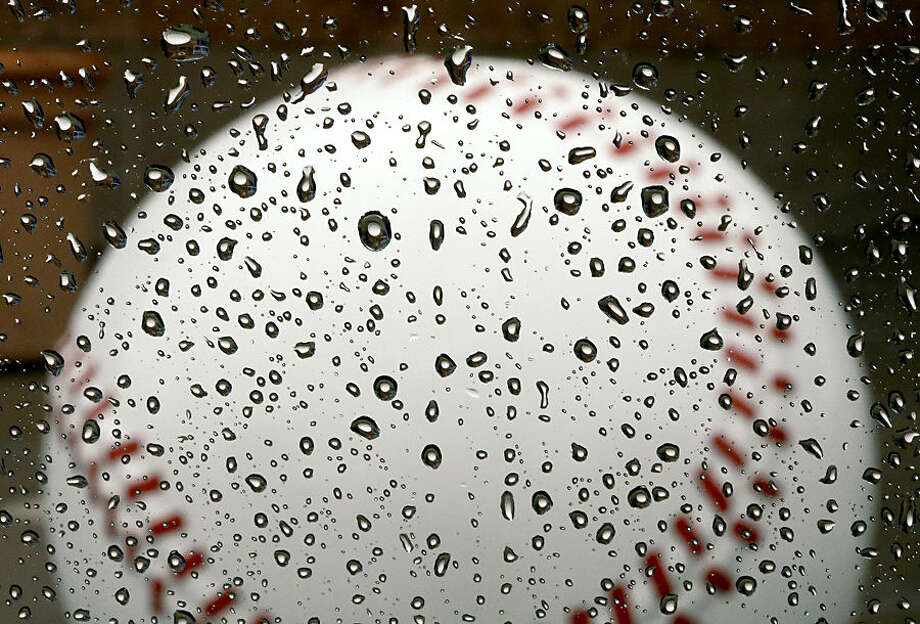 A large concrete baseball is reflected in raindrops on a window at the Peoria Sports Complex where the Seattle Mariners and the San Diego Padres hold their spring training baseball practice Monday, March 2, 2015, in Peoria, Ariz. A steady morning rain kept the teams from practicing outside as they prepare for their first spring training games on Wednesday. (AP Photo/Charlie Riedel)